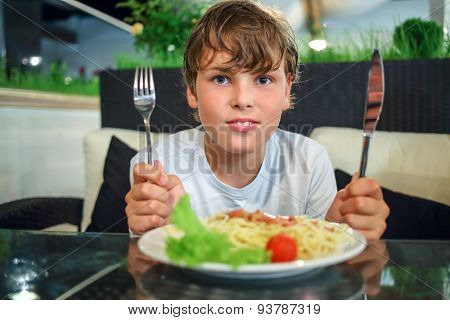 boy with a knife and fork in front of a plate of pasta