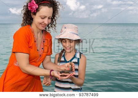 Girl with her mother holding freshly caught fish
