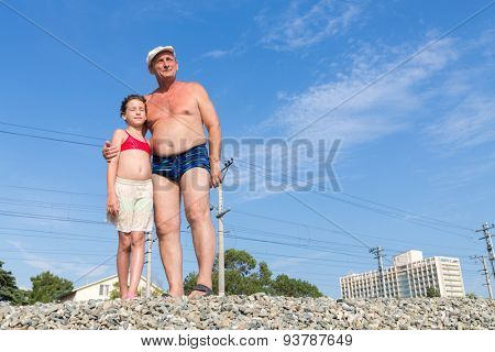 Grandfather with his granddaughter on the railway embankment