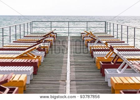 deck chairs on the pier in the sea