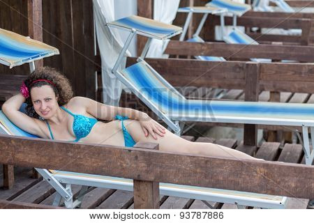 a woman in a bathing suit lying on a deckchair