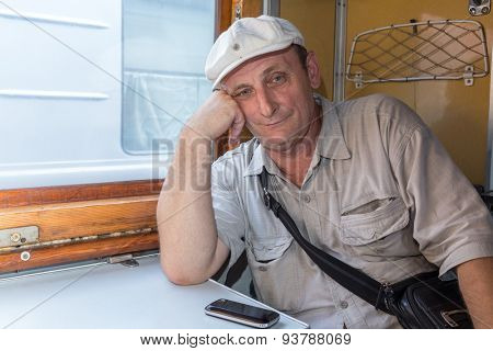 man sitting with his elbows on the table in a train