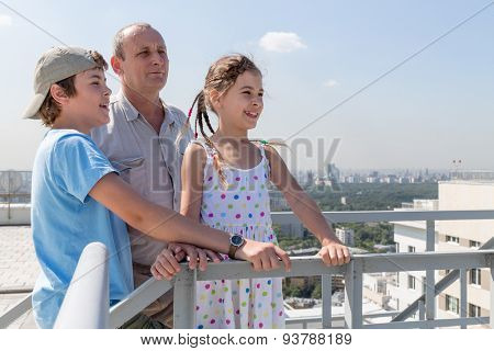 Grandfather with grandson and granddaughter admire the city view from the roof