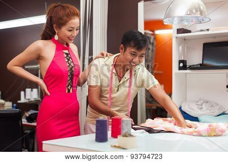designer asian man tailor shop working on table with woman customer fashion