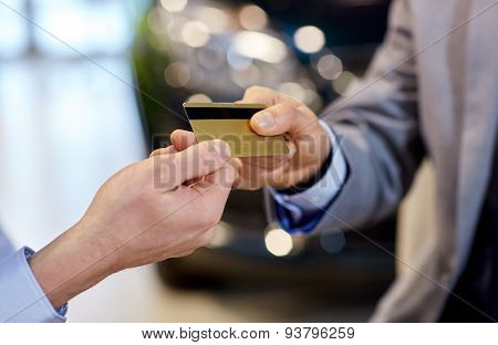 auto business, sale and people concept - close up of customer hand giving credit card to car dealer in auto show or salon