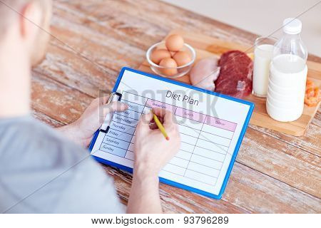sport, fitness, healthy lifestyle, diet and people concept - close up of male hands with food rich in protein on cutting board on table