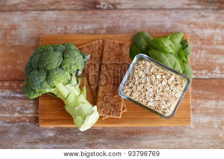 healthy eating, diet and fiber rich in food concept - close up of broccoli, crispbread, oatmeal and spinach on wooden table