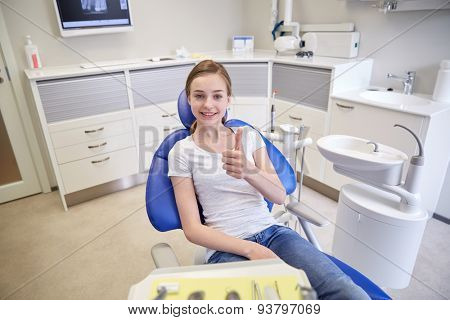 people, medicine, stomatology and health care concept - happy patient girl showing thumbs up at dental clinic office
