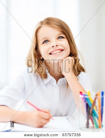 education, creation and school concept - smiling little student girl drawing and daydreaming at school
