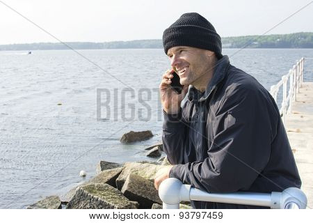 Man Talking On Phone At End Of Breakwater In Bay