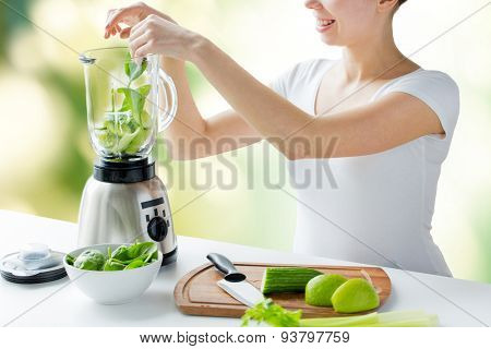 healthy eating, cooking, vegetarian food, dieting and people concept - close up of young woman with blender and green vegetables making detox shake or smoothie over natural background