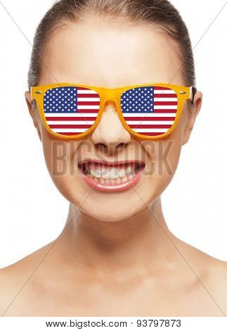 people, patriotism, national pride and independence day concept - happy teenage girl in shades with american flag