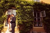 foto of ivy  - Bride and groom embracing in front of a beautiful house covered with ivy