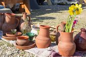 image of pottery  - pottery utensils glass and flowers on the ground - JPG