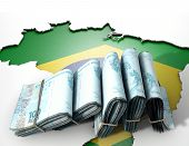 stock photo of brazilian money  - The shape of the country of Brazil in the colours of its national flag recessed into an isolated white surface with a wad of folded Brazilian real notes resting on it - JPG