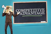 picture of anonymous  - Anonymous businessman holding a megaphone against competitive advantage written on a chalkboard - JPG