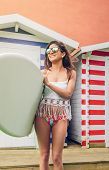 foto of beach hut  - Portrait of beautiful young surfer woman with white top and bikini holding surfboard over a beach striped huts background - JPG