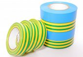 image of insulator  - Closeup of multicolored insulating tapes isolated on white background - JPG