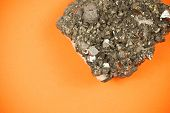 Постер, плакат: Piece of black lead ore with irregular texture shot on orange paper background