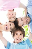 stock photo of huddle  - Happy family forming a huddle - JPG