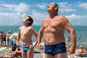 foto of grandfather  - Grandfather with his grandson bask in the sun on the beach - JPG