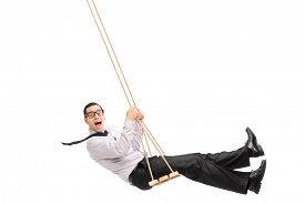 picture of swing  - Delighted young man swinging on a swing and looking at the camera isolated on white background - JPG