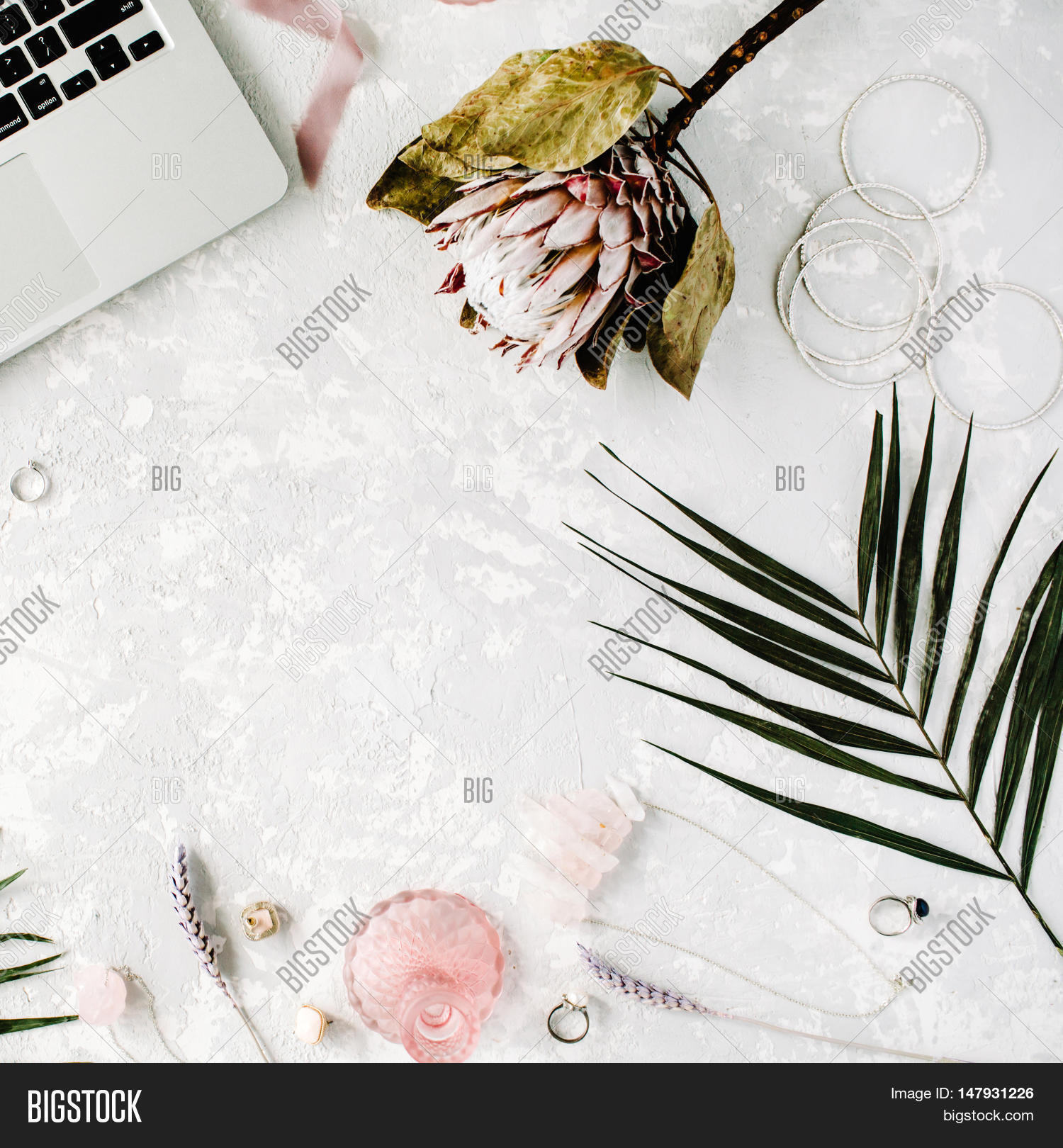 flat lay feminine home office workspace with laptop proteus flower necklace palm branches and accessories