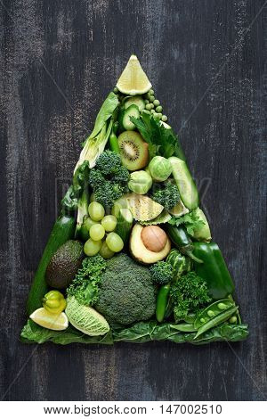 Overhead series of assorted fresh organic raw green colored vegetables in shape of triangle pyramid, part of a food collection set