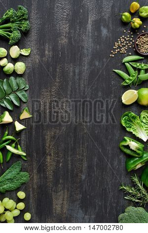 Variety of raw green produce fresh organic vegetables on dark rustic background, forming frame copyspace for poster website book magazine