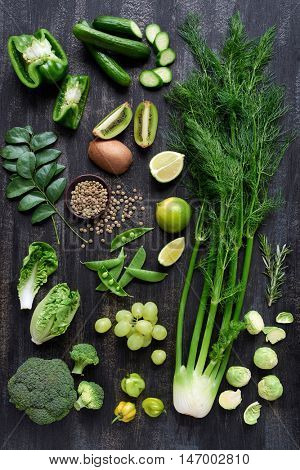 Collection of fresh green vegetables on dark rustic distressed background, broccoli, lettuce, beans, capsicum, peppers, peas, brussels sprouts, kiwi, cucumber