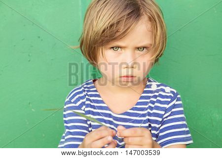 Little girl in a striped dress with a scowl on her face