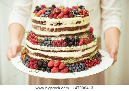 Wedding cake in two tiers with fresh berries holding