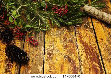 Winter background. Composition with fir branches, fir cones, branches with berries dogwood on a red shabby wooden background. Selective focus