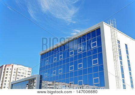 Grodno, Belarus - August 8, 2016: A modern rectangular building in a residential area made of white panels and mirrored glass walls reflecting the blue sky. Grodno, Belarus.