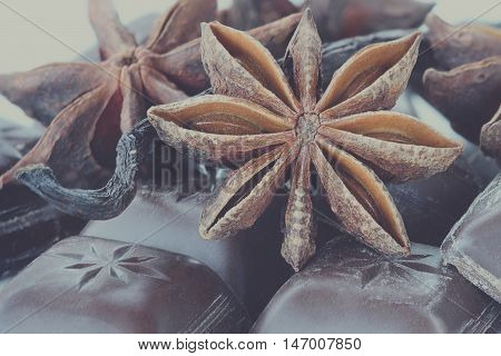Close up of Star of Anise Chocolate bars and Vanilla pods. Extreme close-up with shallow depth of field. Selective focus on center of Anise star.