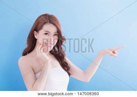Beauty woman with charming smile and show something to you with health skin and hair isolated on blue background asian beauty