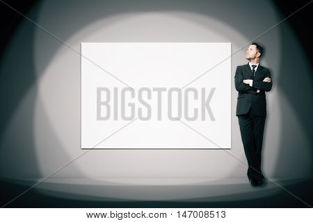 Businessman standing next to blank white billboard with spot lights in concrete room. Mock up 3D Rendering