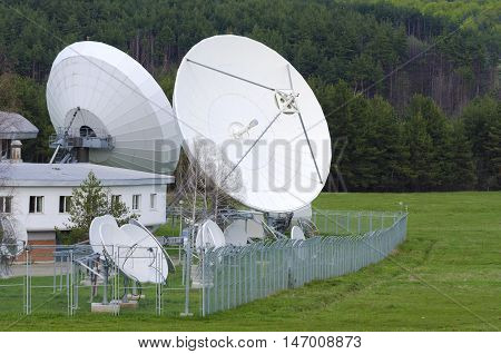 Satellite dishes in a countryside. Metal fence