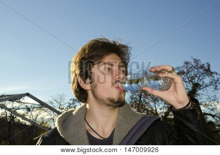 Teenager drinking mineral water in a bottle in a park
