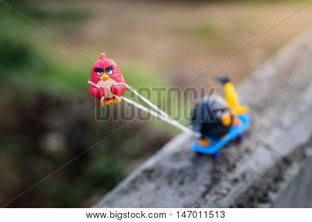 Chiang Mai Thailand - June 13 2016: Red Angry bird Pull his friends up the hill with a rope attached to skateboard with anger.