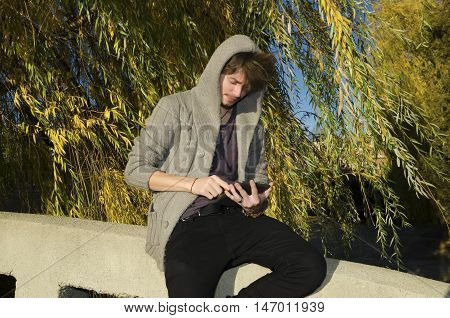 Teenager reading electronic book in the park in autumn