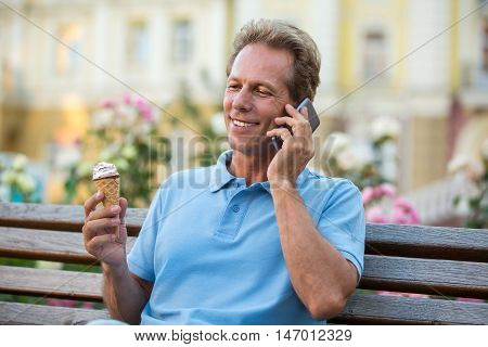 Man with phone is smiling. Mature guy holds ice cream. This story never gets old. Rest in the park.