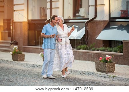 Mature couple walking and smiling. Man and woman holding hands. Cheerful stroll at daytime. Cherish every moment together.