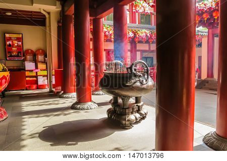 SINGAPORE, REPUBLIC OF SINGAPORE - JANUARY 09, 2014: Chinese Incense stick in a pot. Interior of the Buddha Toothe Relic Temple, Chinatown, Singapore city