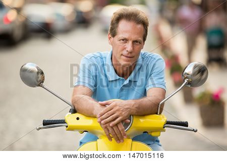 Adult man sitting on scooter. Guy in t-shirt slightly smiling. Daytime trip around the city. Few minutes of break.