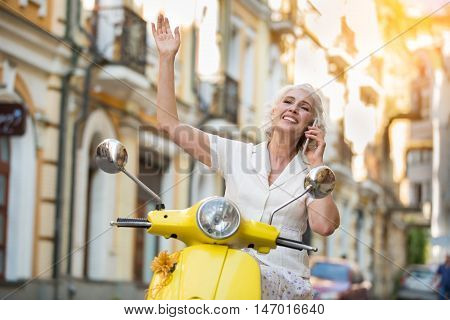 Mature lady with phone smiling. Woman on scooter waving hand. So glad to hear you. Feeling of elation.