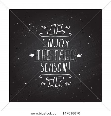 Hand-sketched typographic element with rubber boots, leaves and text on blackboard background. Enjoy the fall season