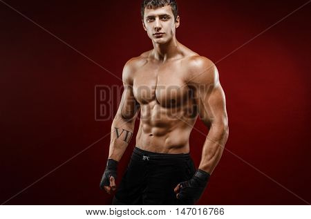 Portrait of topless young muscular man with roman numerals on arm in fighting gloves on red background