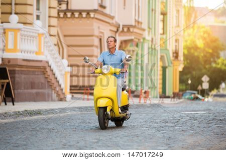 Adult man riding a scooter. Yellow scooter on empty road. Need to move faster. No traffic jams.
