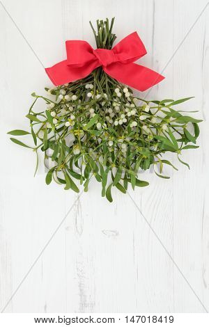 Christmas mistletoe decoration with red ribbon bow over distressed white wood background.